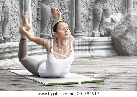 Beautiful strong Woman doing yoga pose in abandoned temple in Bali