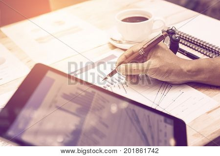 Hand Businessman Pointing On Summary Chart Report And Holding Tablet For Looking Data Information.