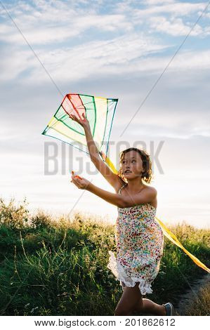 Girl in dress holding bright kite while running and looking away in green summer field.