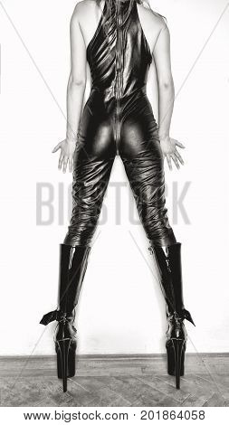 Sexy dominatrix posing at wall in black latex catsuit and boots