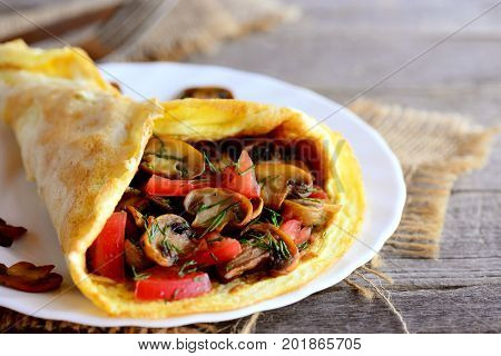 Omelette stuffed with fresh tomatoes slices and fried mushrooms on a serving plate. Healthy mushroom omelette slimming world. Closeup