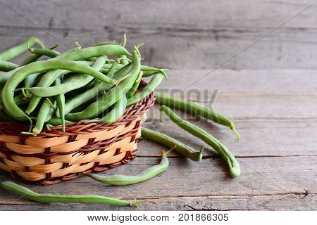 Raw green beans in a brown wicker basket and on an old wooden background. Raw diet food. Vegan food