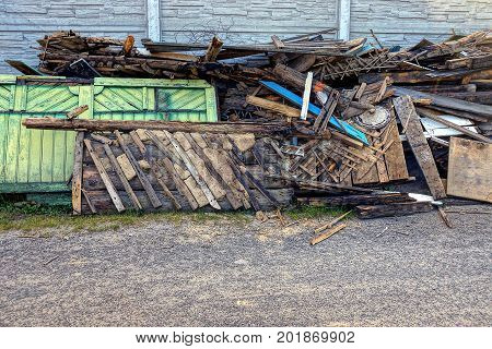 pile of rubbish from old planks in the courtyard in the street