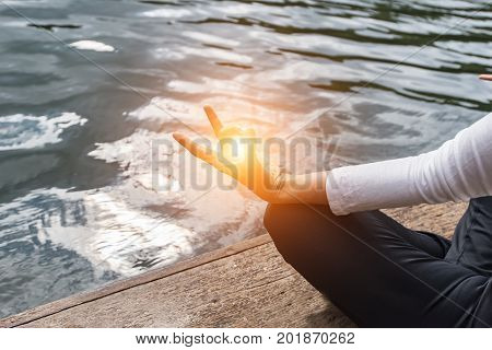 Close up of female hand zen gesturing. Girl sits in asana position.Close up hand. Woman do yoda outdoor. Woman exercising yoga at the nature background select focus