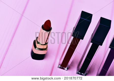 Various Lipsticks On Pink Wooden Background
