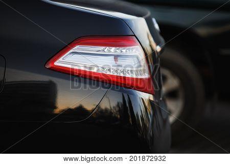 Car headlight. Back light of city car on blurred black background