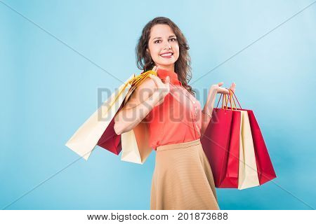 Beautiful young woman holding shopping bags on blue background. Discount, sale, buy and shopaholic concept.