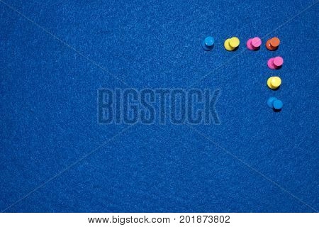 Colored pins on a board on a blue bulletin board