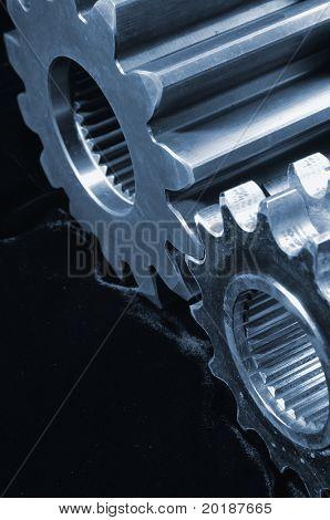 bluish gears, cogwheels against black velvet