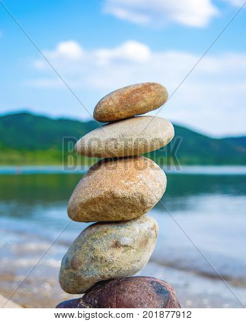 Photo of stones balanced on top of eachother on a sandy beach