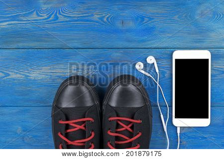 Overhead view of sports shoes by mobile phone with isolated screen and in-ear headphones on blue wooden table floor. Empty space for text copy space empty blank screen