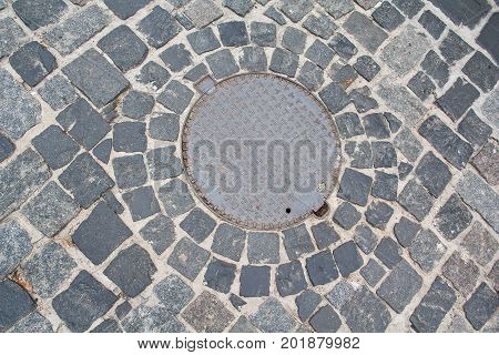 Metal sewer hatch on the stone pavement. Backgrounds and textures