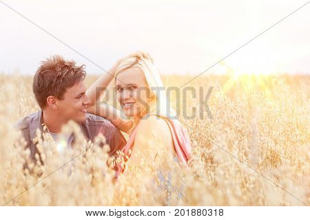 Portrait of beautiful young woman sitting with boyfriend amidst field