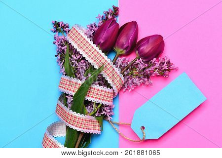 Concept of spring with pink tulip flowers and lilac near cyan note card on bicolor pink and turquoise background top view