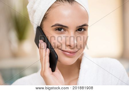 happy woman in bath robe relaxing after spa pedicures and using smartphone