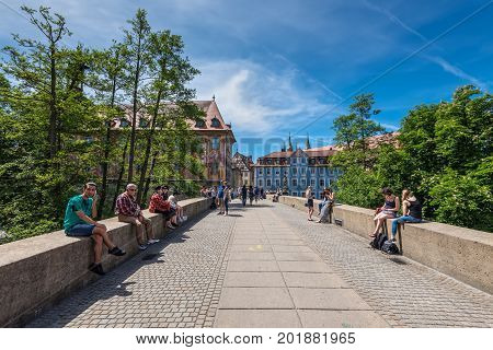 Bamberg Germany - May 22 2016: People seating and passing by bridge in downtown of Bamberg Upper Franconia Bavaria Germany. Bamberg is under UNESCO protection.
