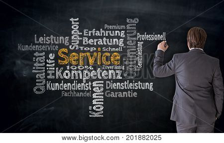 Businessman Writes Service (in German Competence, Consulting) Cloud On Blackboard Concept