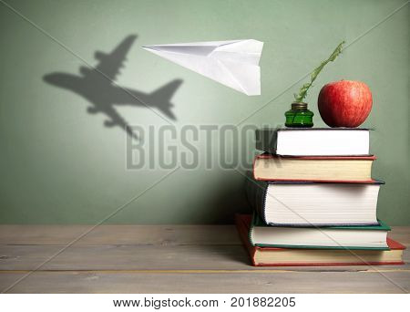 Success concept, paper plane with shadow of an aircraft next to a stack of books quill and apple