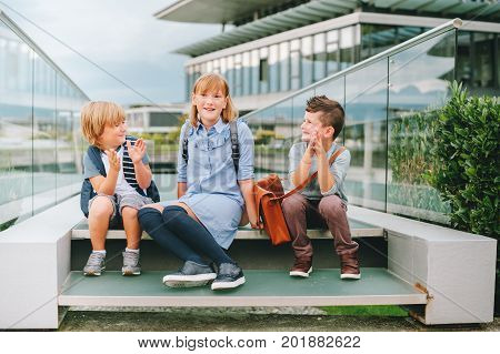 Group of 3 funny schoolkids posing outdoors wearing backpacks. Back to school concept. Fashion for children