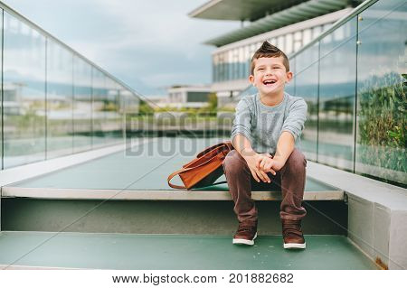 Outdoor portrait of happy young kid boy. Fashion schoolboy resting outside. Back to school concept