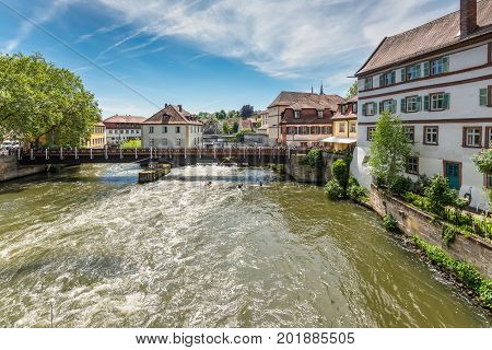 Bamberg Germany - May 22 2016: Tourists on a bridge and Kayaks slalom on the River Regnitz Bamberg Bavaria Germany Europe. The historic city center of Bamberg is a listed UNESCO world heritage site.
