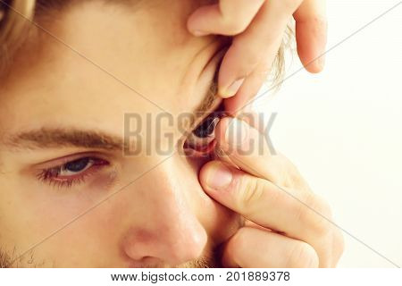 Guy holds corrective lense on his finger isolated on white background selective focus. Man with beard and blue eyes puts contact lenses on close up. Health ophthalmology and vision concept