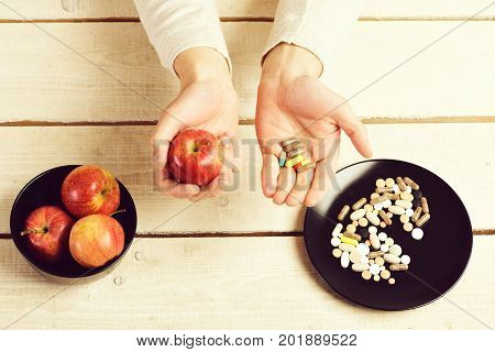 Male hands hold apple and pills at wooden table. Guys hands on light background and bowl of fruit with plate of medicine. Organic food diet and traditional drugs treatment. Healthy choice concept