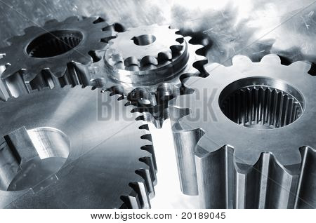 industrial gear mechanism mirrored in steel background all in a metallic blue toning