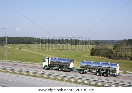 fuel truck on the go driving on highway with country-side