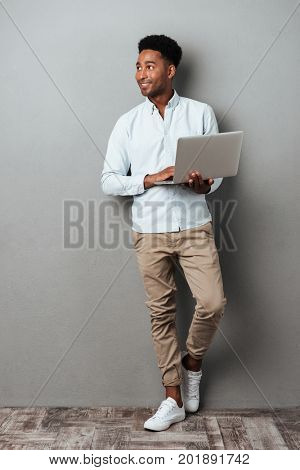Full length portrait of a young smiling african man standing with laptop computer and looking away isolated over gray background
