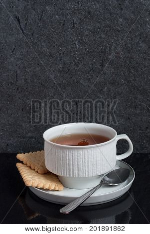 A vertical view of  a cup of tea with two square biscuit crackers are laid on a black background with a reflection with copy space above