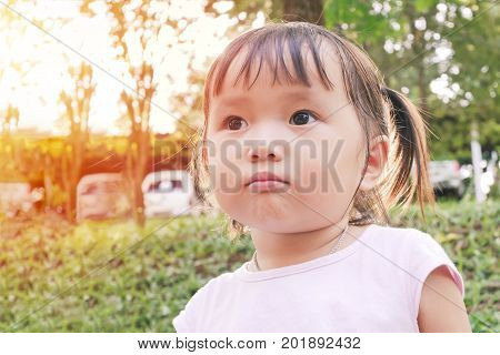 portrait of little girl scowling face in the green garden with warm tone and soft focus asian baby