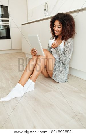 Vertica image of smiling african woman sitting on the floor on kitchen at home and using tablet computer