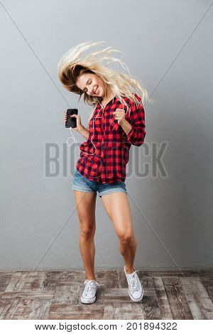 Photo of happy young blonde woman standing isolated over grey wall. Listening music by phone shaking hair.