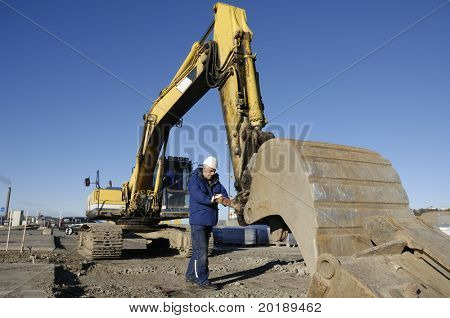 driver examining scoop on bulldozer, digger
