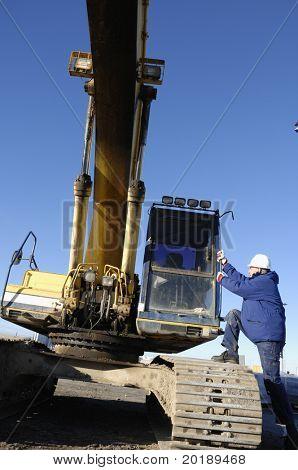 driver boarding large bulldozer, digger
