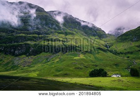 Small house under waterfall and mountain in dreamy rainy fog weather. Countryside in Glencoe Scotland United Kingdom. Soft light and calm mood.