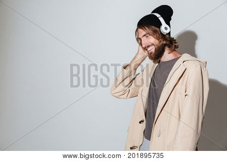 Picture of a handsome hipster man looking aside isolated over wall background listening music with headphones.