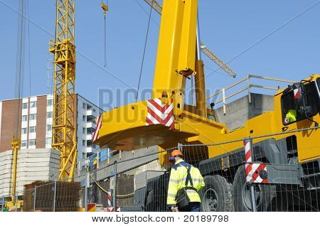 mobile cranes inside construction site, engineer passing by.