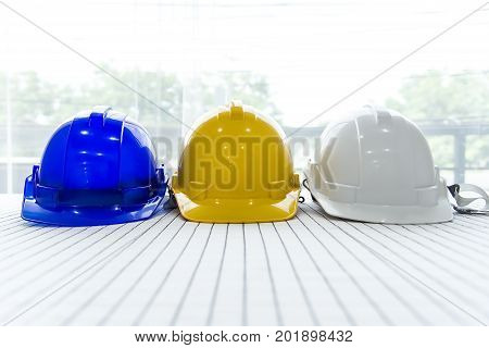 white yellow and blue hard safety helmet hat for safety project of workman as engineer or workerindustrial