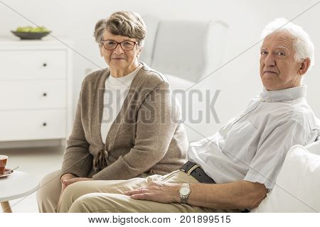 Couple of elder people sitting together on white coach next to coffee table