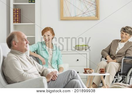 Young assistant talks with two elder people in retirement home