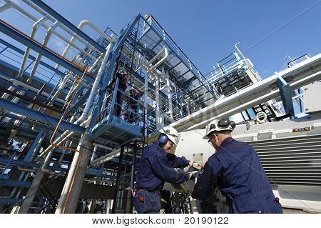 engineers working inside oil and gas refinery, pipelines and storage