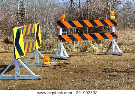 A construction and detour sign blockage along a gravel road