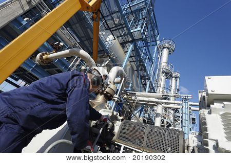 chemical engineer examining pipelines construction inside oil refinery