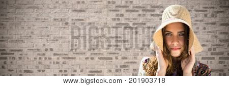 Digital composite of Portraiture of woman holding sun hat against brown brick wall
