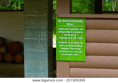 A be environmentally wise about firewood sign.