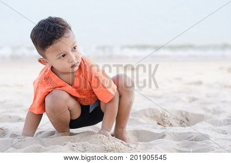 Boy about 4-5 years old playing white sand on beach alone with sadness.