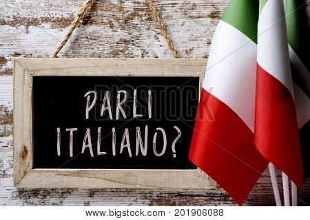 a wooden-framed chalkboard with the question parli italiano? do you speak Italian? written in Italian, and some flags of Italy against a rustic wooden background