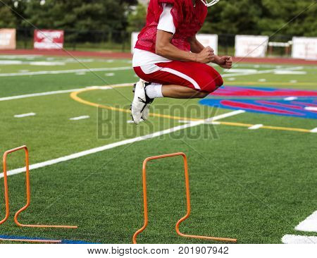 A high school athlete jumping over hurdles on a green turf field during pre-season football practice.
